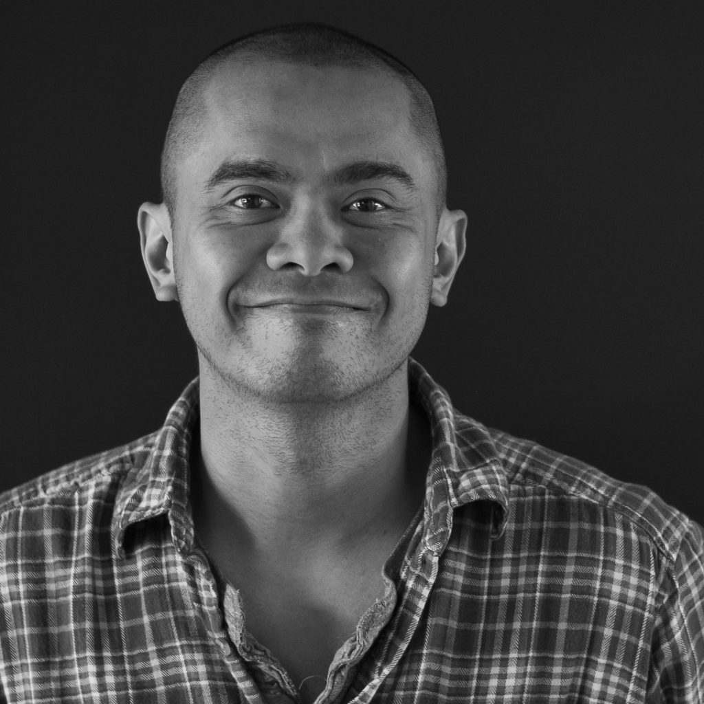 PLUS QA Analyst Marvin smiling at the camera for a headshot.