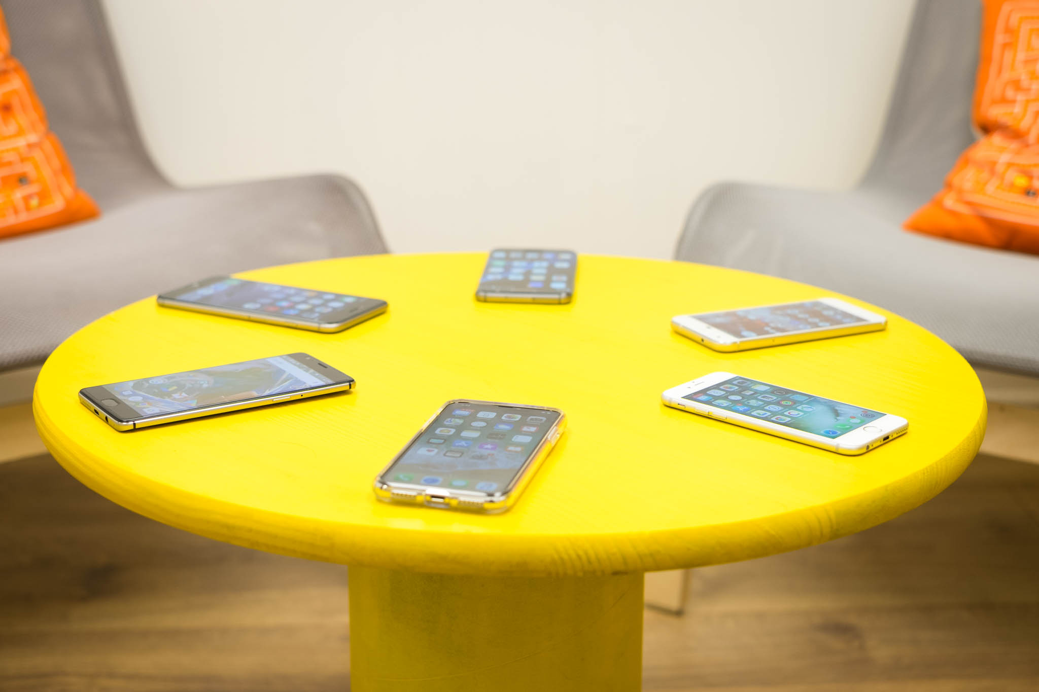 Image of six smart phones laying around a circular yellow table