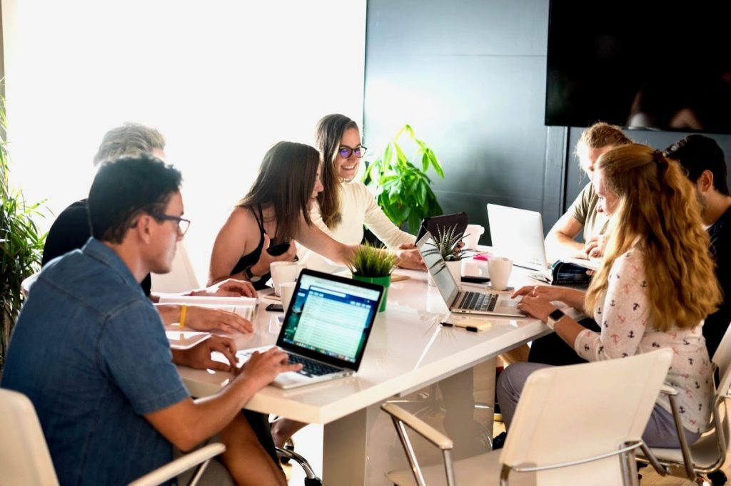Team of QA testers sits around a conference room table looking at laptops and talking together.