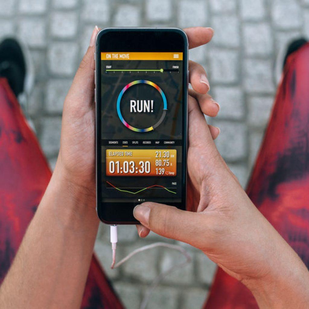 Runner using healthcare technology app on her smartphone