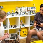 Two testers usability testing in yellow room filled with legos