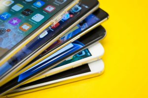 Six iPhone stacked on top of one another on top of yellow background