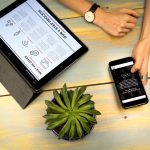Hand holding phone and tablet and plant on top of a desk