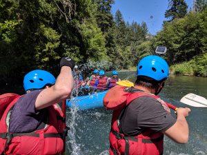 Photo of PLUS QA team splashing coworkers on white water rafting company trip