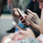 Photo of group of hands holding smartphones