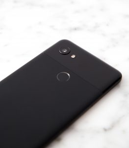 Close up of the back of a black Android Pixel on top of a marble background