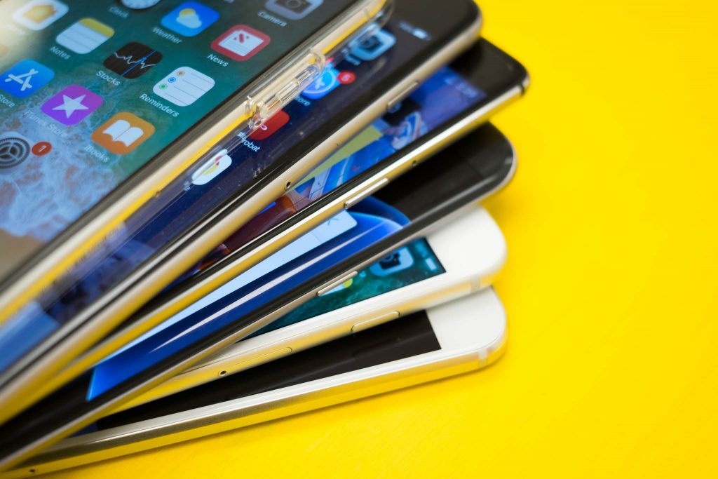 Stack of mobile devices on top of a yellow background