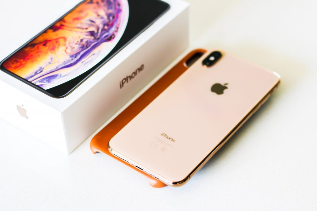 Image of iPhone X on top of phone case, next to original iPhone box packaging