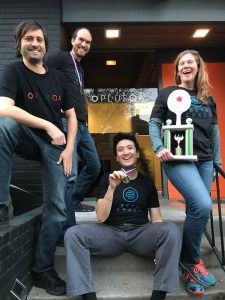 Picture of four PLUS QA employees holding trophy and medals from ping pong champions