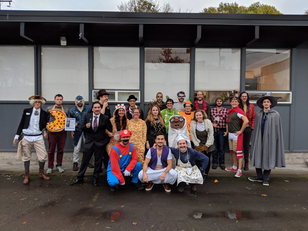 Photo of PLUS QA employees dressed up in Halloween costumes