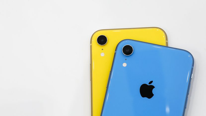 Image features two iPhone XR smartphones — one yellow, one blue — stacked on top of one another.