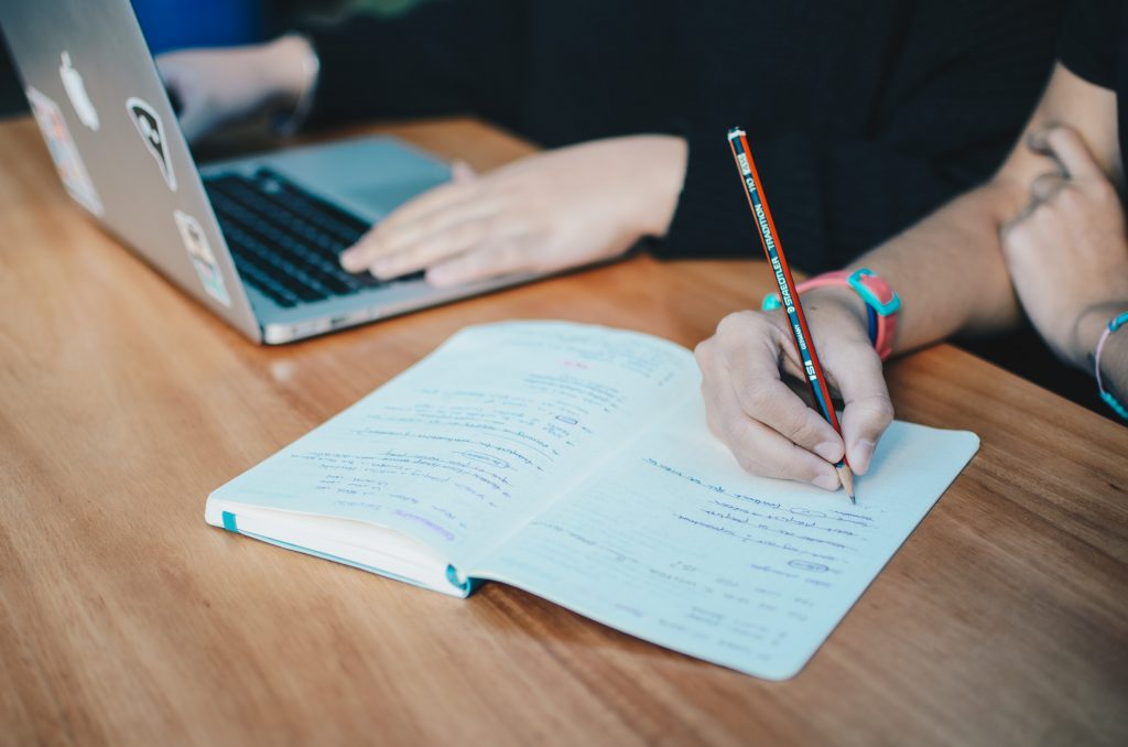 Image of two pairs of hands, one on a laptop and one writing in a notebook
