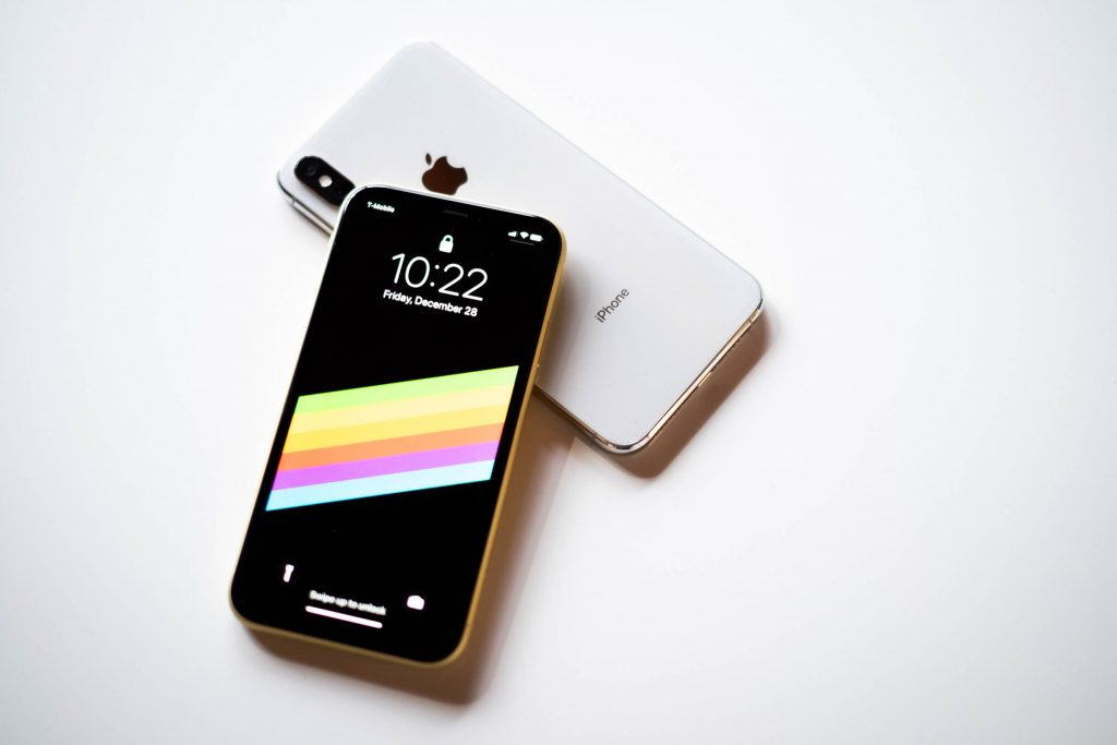 Two iPhones, one facedown and one face up on top of the other, both on top of a white background