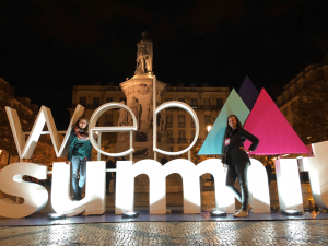 Photo of Web Summit sign in Lisbon, Portugal, with two PLUS QA employees standing in front of it