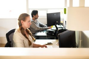 Image of a female tester and a male tester at their desks looking at their computers