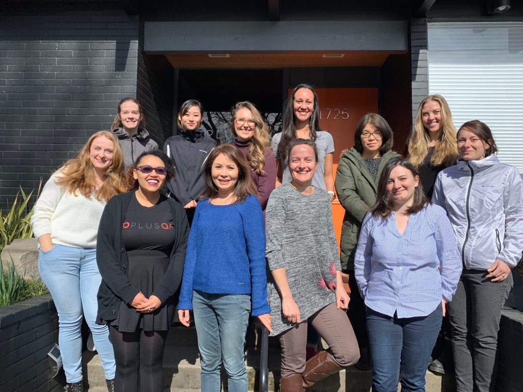 Photo of the women employees at PLUS QA on the steps in front of the office