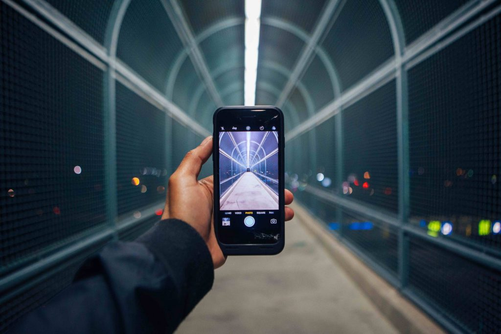Man pointing his phone in a tunnel