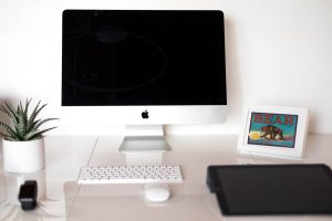 image of workstation, with an iMac, a keyboard, a mouse, a plant, and a picture frame