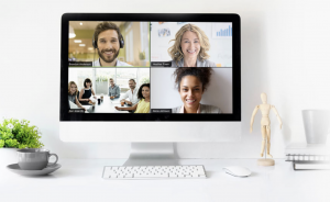 image of an iMac with four people on the screen, doing a video call with Zoom