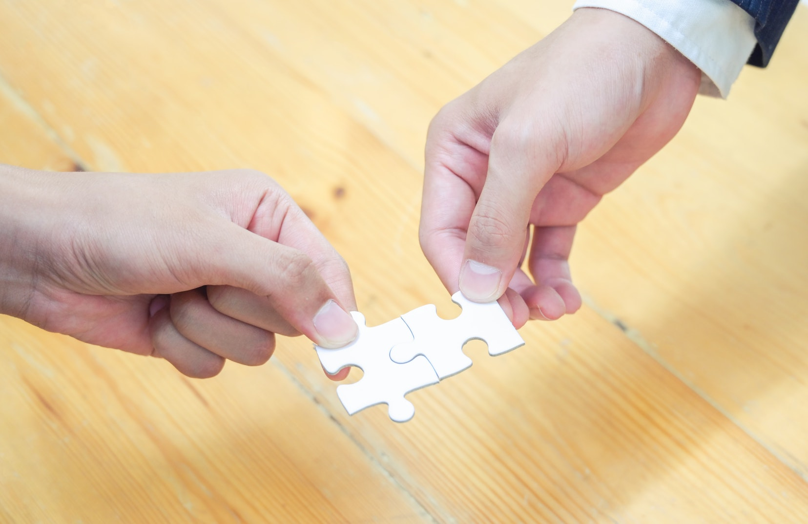 Two people connecting puzzle pieces