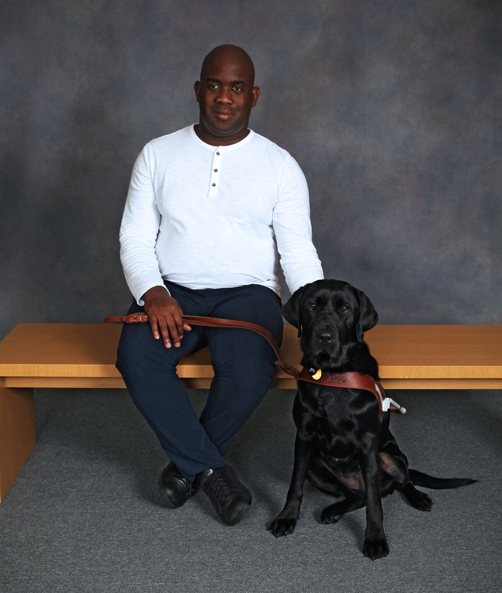 Abdul sitting with his guide dog Faye