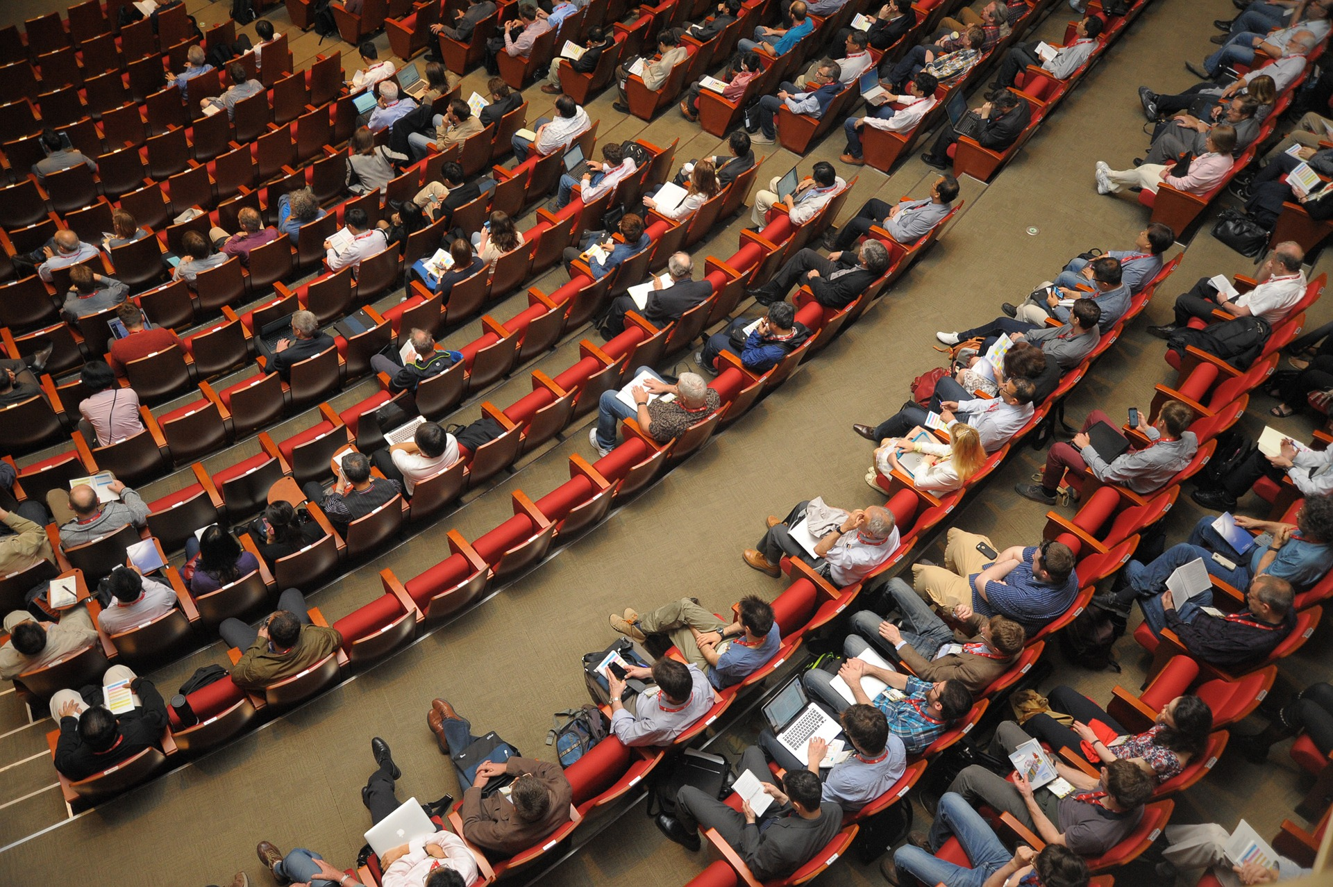 A view from above of people sitting in an auditorium, many with laptops and tablets