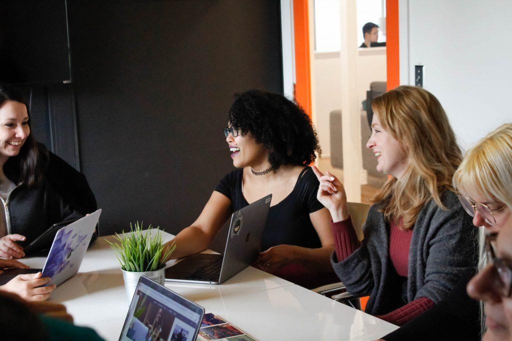 Women in a team meeting at PLUS QA