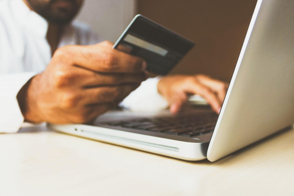 Someone about to engage in e-commerce, with their hand holding a red credit card above the keyboard of a laptop, with eBay visible on the laptop screen
