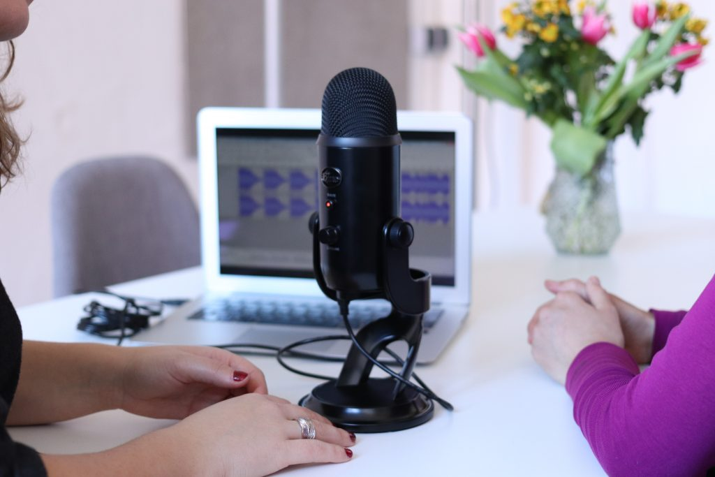 A podcast microphone on a table in front of an open laptop recording the voices of two women whose arms are visible