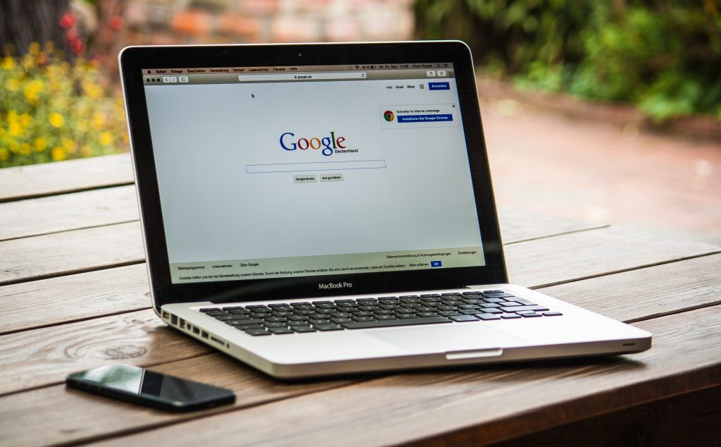 A MacBook Pro open to Google on a web browser, sitting on a picnic table outside.
