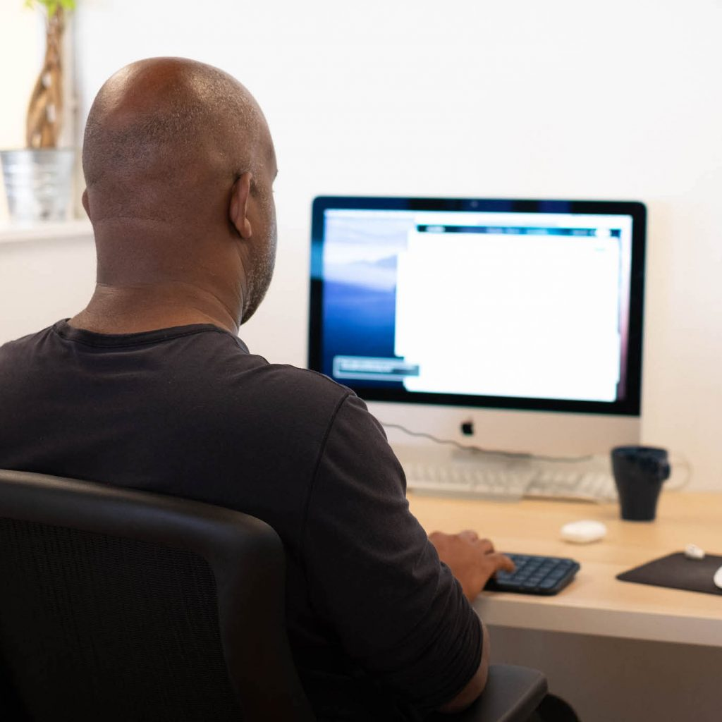 A person sitting at a desk, with headphones connected to the iMac they're using voiceover on.