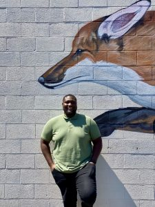 Web QA analyst Royus standing in front of a mural of a fox.
